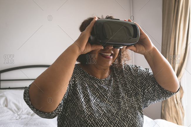 Senior woman using virtual reality headset in bedroom at home