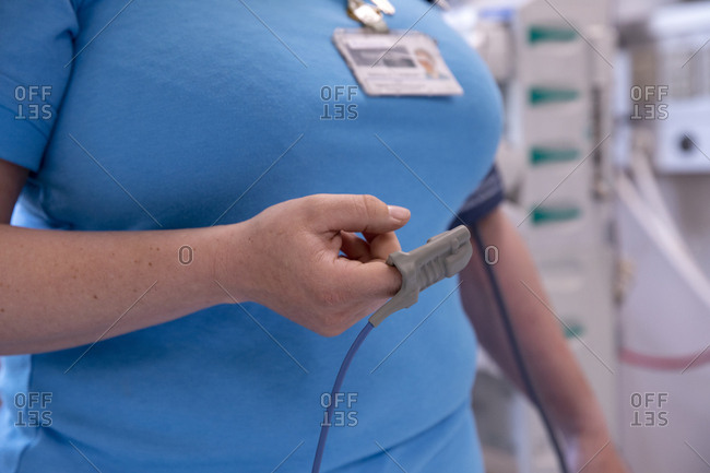 Midsection of female doctor using pulse oximeter in hospital