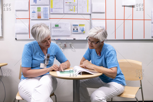 Female doctors discussing medical records while sitting on chairs in hospital