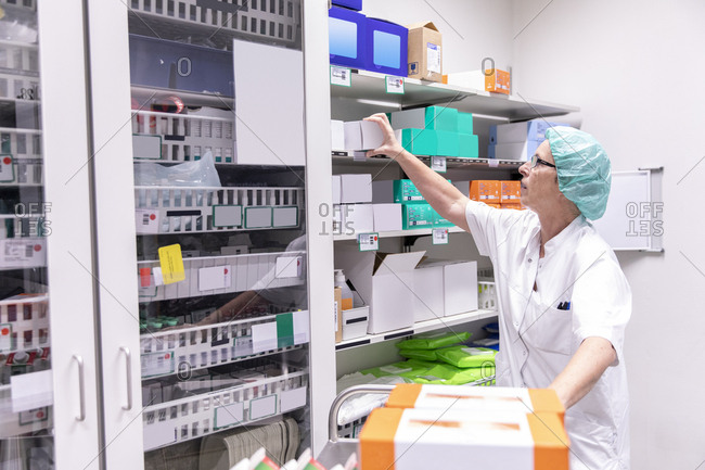 Female doctor looking medicine boxes in storage room at hospital