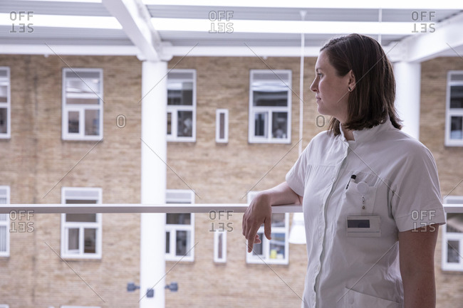 Thoughtful female doctor looking away while standing by railing in hospital