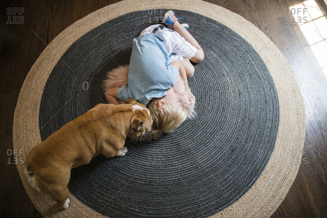 High angle view of pug standing by boy sleeping on carpet at home