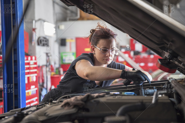 Female mechanic repairing car engine in auto repair shop