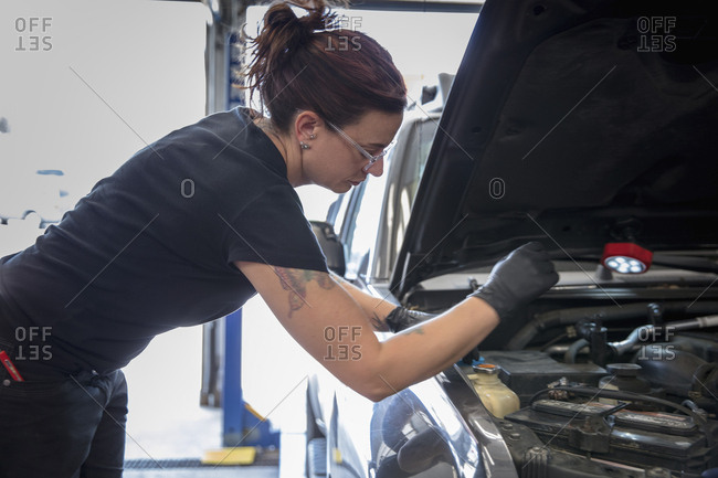Side view of female mechanic repairing car engine in auto repair shop