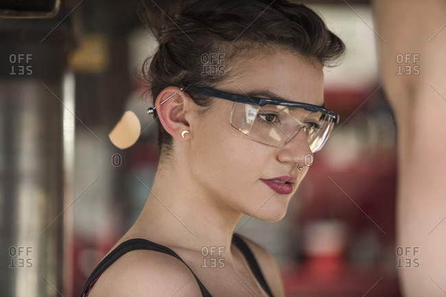 Female mechanic wearing protective eyewear while working in auto repair shop