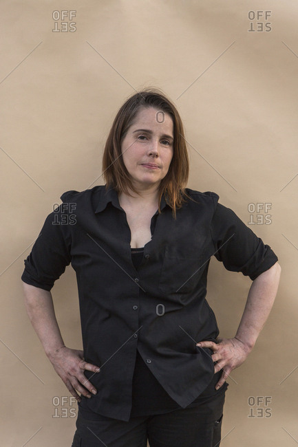 Portrait of confident woman with hands on hip standing against colored background