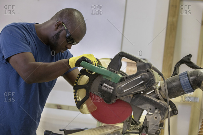 Carpenter cutting wood with circular saw while standing in workshop