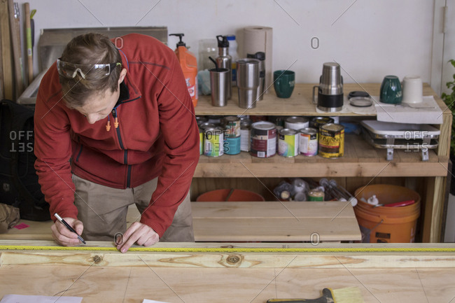 Carpenter measuring wood with tape while standing in workshop