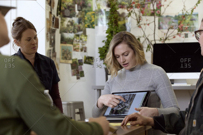 Businesswoman explaining to female coworkers over tablet computer while sitting in workshop
