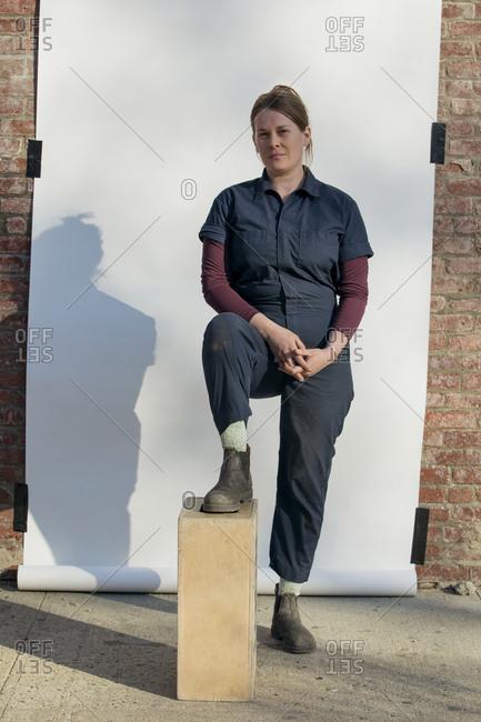 Portrait of confident female entrepreneur standing on sidewalk against white backdrop