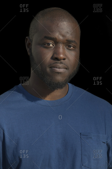 Close-up portrait of confident businessman standing against black background