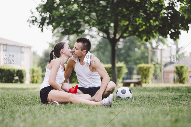 Young couple kissing while sitting on soccer field at park
