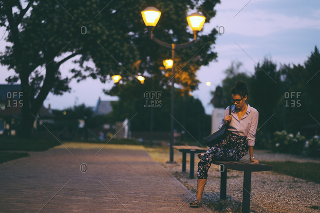 Thoughtful young woman sitting on bench at park during dusk