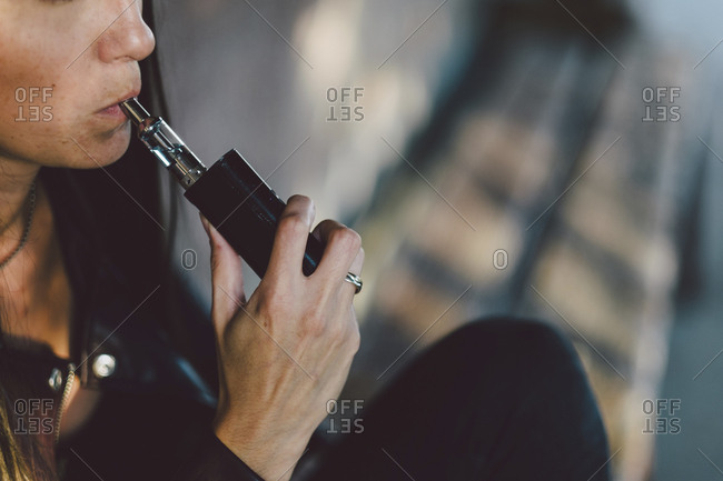 Midsection of young woman smoking electronic cigarette while sitting against wall on footpath