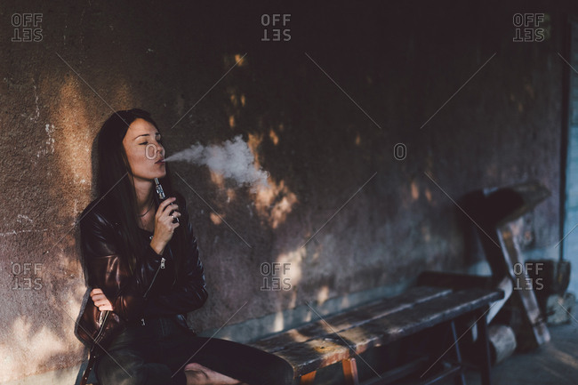 Young woman smoking electronic cigarette while sitting on bench against wall on footpath