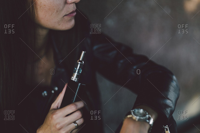 Midsection of young woman holding electronic cigarette while sitting against wall on footpath