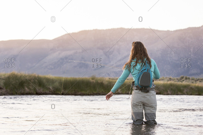 Rear view of young woman with backpack fly-fishing in Owens River against mountains