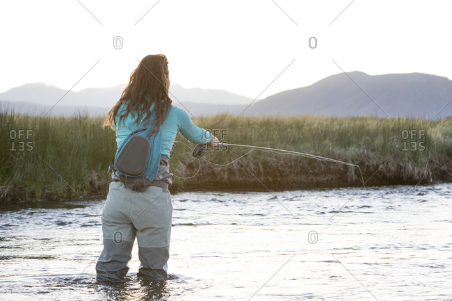 Rear view of young woman fly-fishing in Owens River against mountains