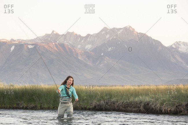 Young woman fly-fishing in Owens River against mountains