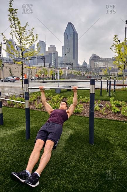Full length of young man exercising using gymnastics bar at park in city