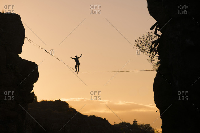 Low angle view of silhouette man slacklining against sky during sunset