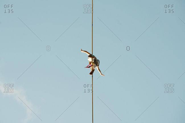 Low angle view of man slacklining against clear blue sky during sunny day