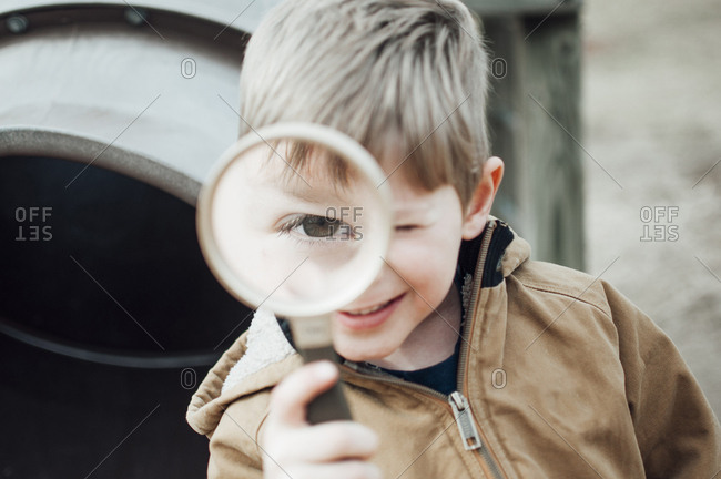 Close-up portrait of happy boy playing with magnifying glass at playground