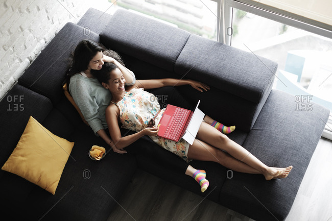 High angle view of lesbian couple watching video over laptop computer while relaxing on sofa in living room