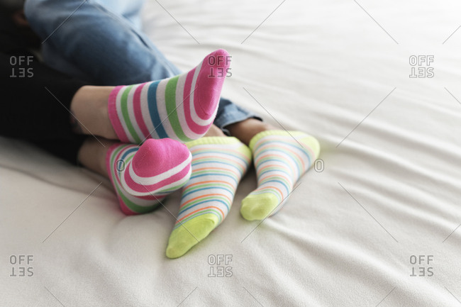 Low section of lesbian couple wearing colorful socks while relaxing on bed at home