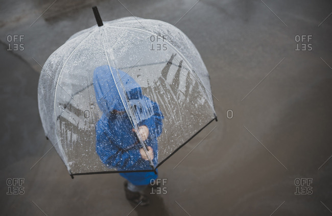 High angle view of boy with umbrella standing on street during rainy season