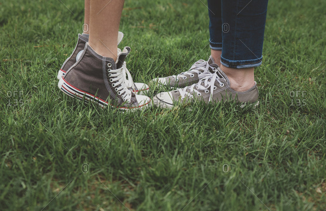 Low section of mother and son wearing shoes while standing on grassy field at park