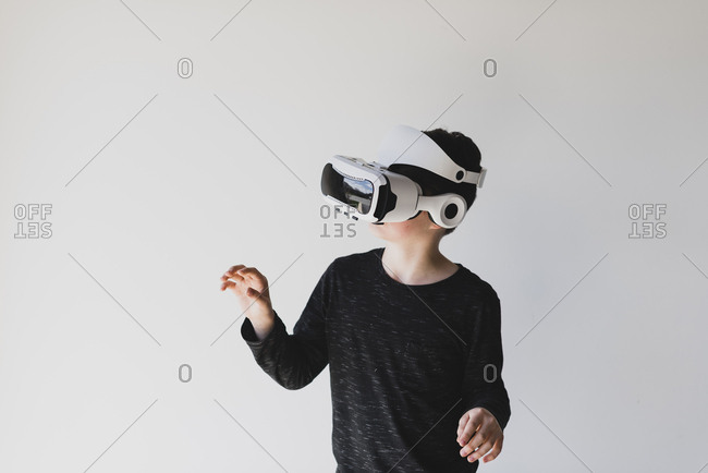Boy using virtual reality while standing against white background
