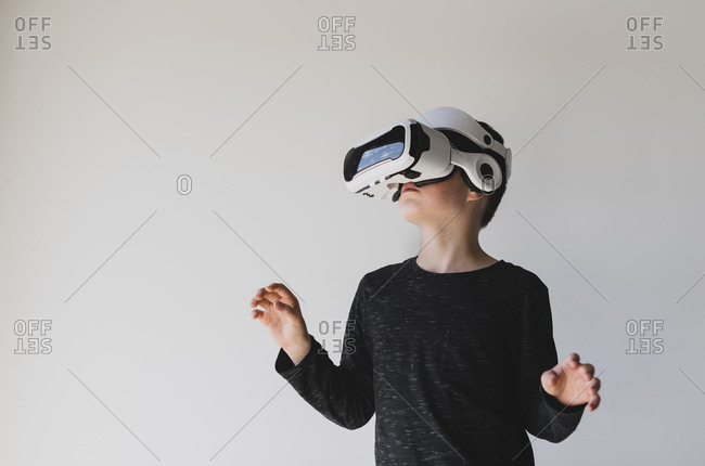 Boy using virtual reality against white background