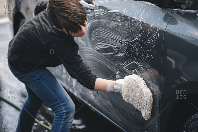 Side view of boy washing car on driveway