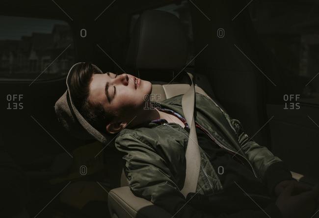 Boy with eyes closed sitting in car