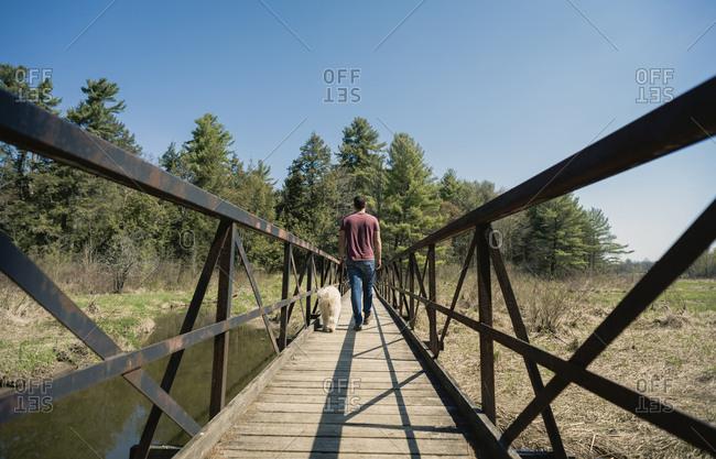 Rear view of man with dog walking on footbridge