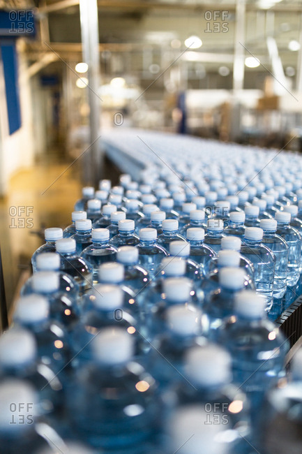 Close-up of water bottles on conveyor belt in industry