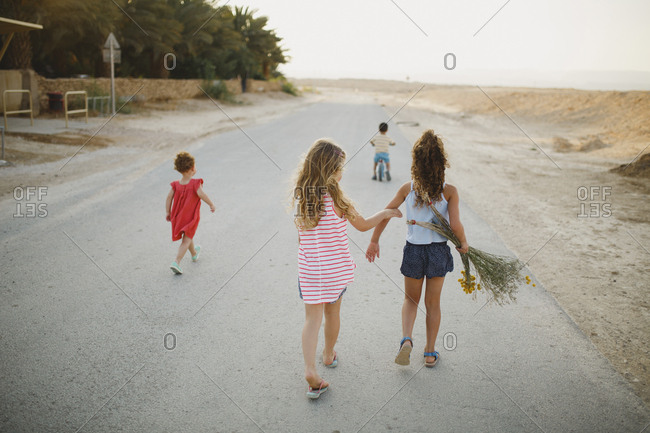 Rear view of sisters walking while brother cycling on country road
