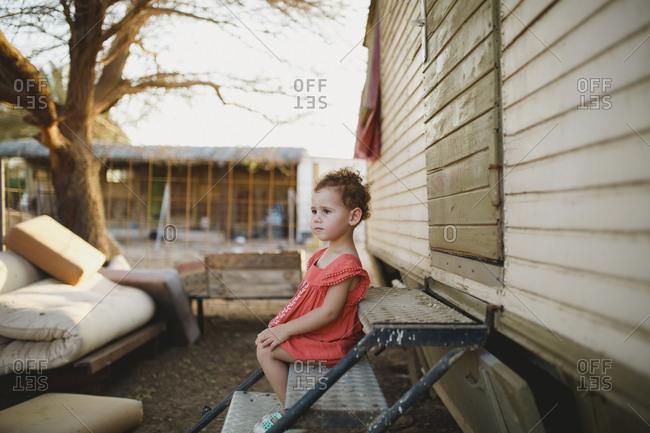 Side view of cute girl looking away while sitting on metallic steps at farm