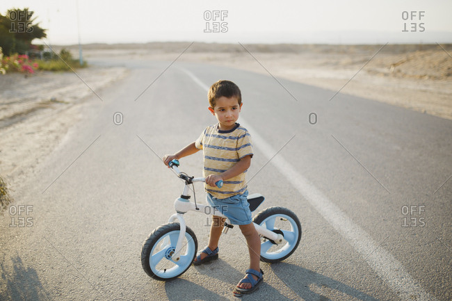 Full length of boy with bicycle looking away while standing on country road