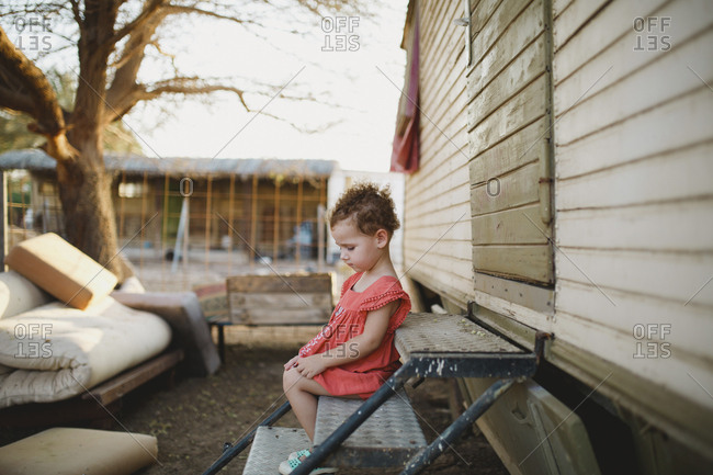 Side view of cute girl sitting on metallic steps at farm