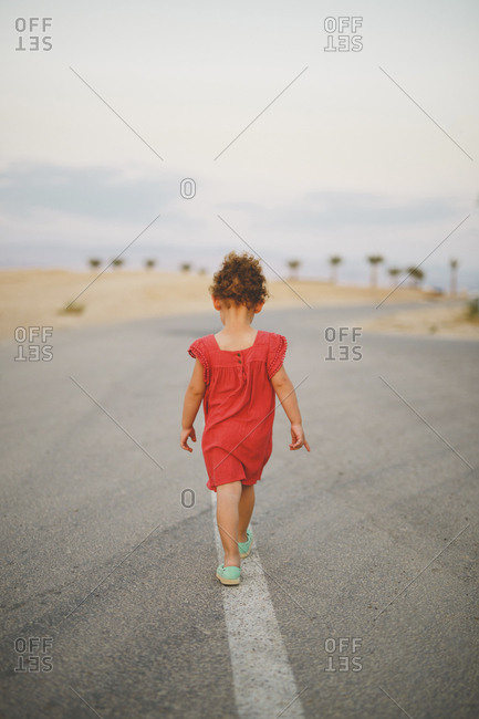 Rear view of girl walking on country road