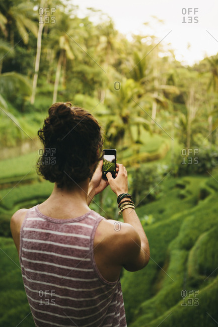 Rear view of man photographing agricultural field with smart phone