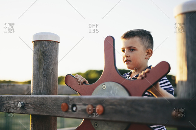 Boy looking away while playing with outdoor play equipment against clear sky during sunset