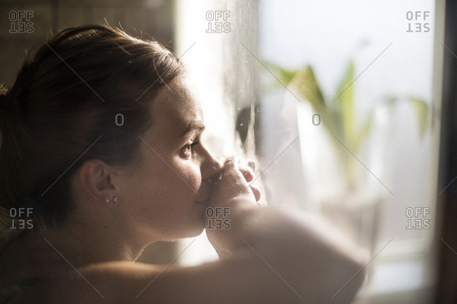 Close-up of pregnant woman in labor at home by window