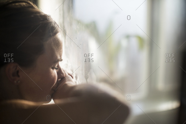 Close-up of pregnant woman with eyes closed in labor at home by window