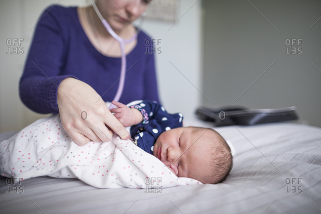 Midwife examining newborn sleeping baby girl with stethoscope on bed at home