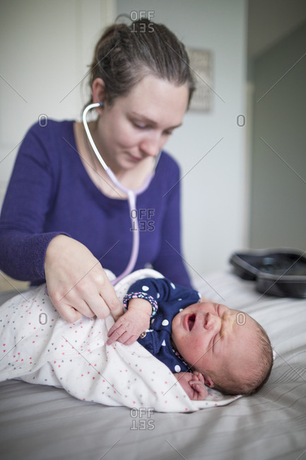 Midwife examining newborn baby girl with stethoscope on bed at home