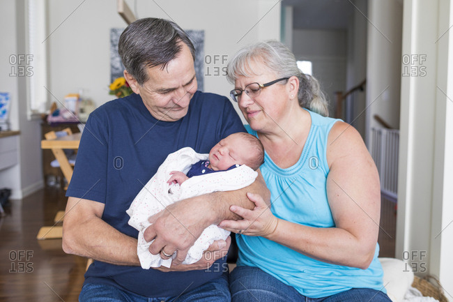 Grandparents with cute newborn granddaughter sitting in living room at home
