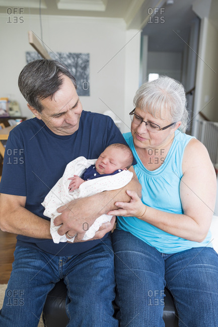 Grandparents with cute newborn granddaughter sitting at home